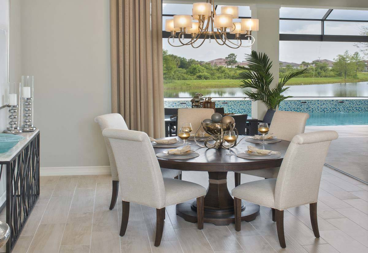 The dining room has gray high back chairs and a round dining table illuminated with glass chandelier.