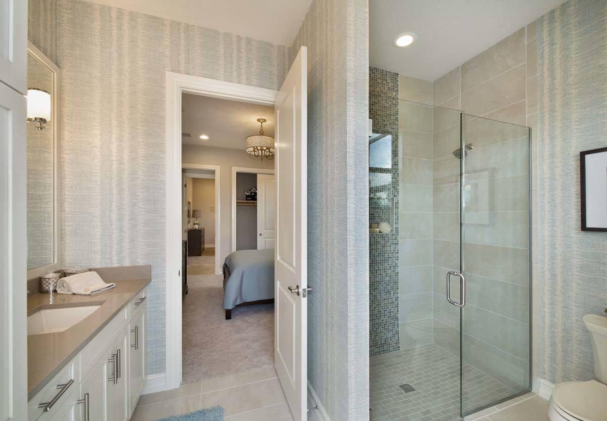 The bathroom is equipped with a walk-in shower, a toilet, and a sink vanity with granite countertop.