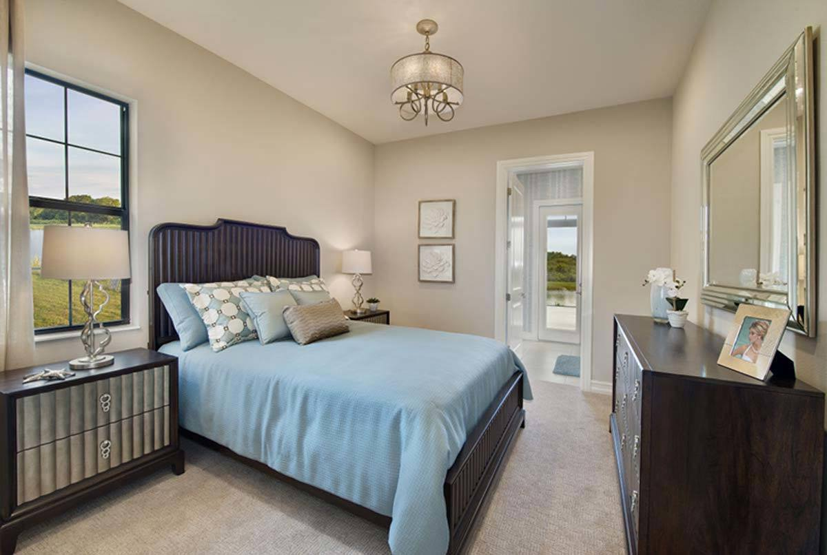 Another bedroom with a wooden dresser and a cozy bed flanked by matching nightstands and classy table lamps.