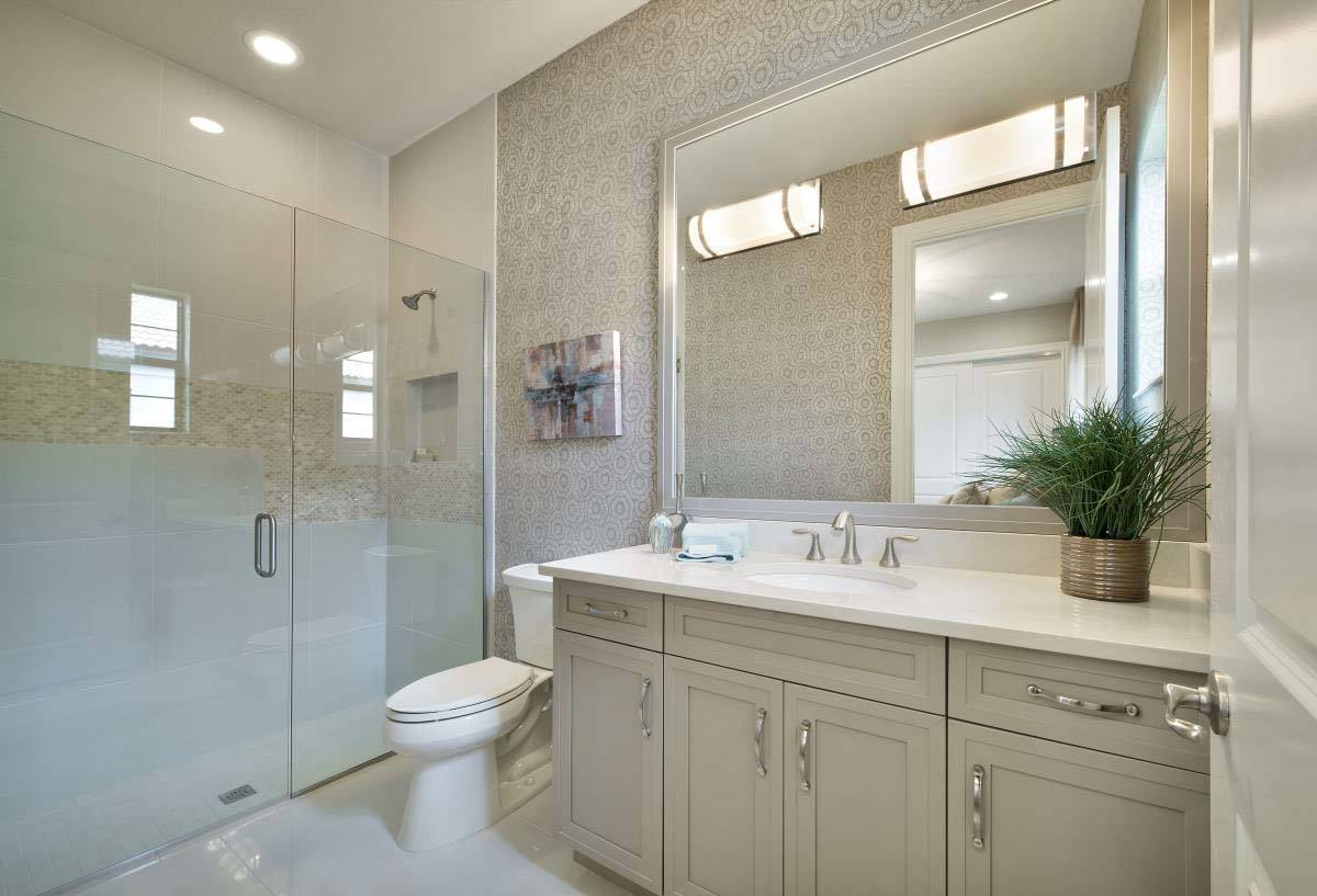 This bathroom has tiled flooring and beige walls adorned with linear mosaic tiles and floral wallpaper.