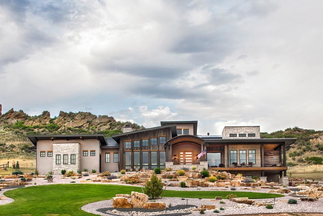 The home's facade is complemented with impressive landscaping that's filled with a lush lawn and desert plants.
