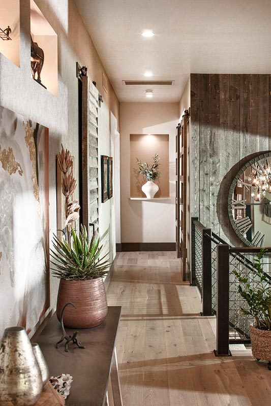 Hallway with natural hardwood flooring and an inset wall occupied by a white flower vase.