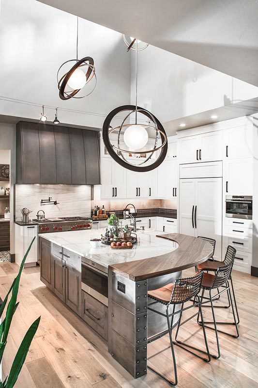 Large spherical pendants illuminate the kitchen with white cabinetry and a center island fitted with a curved eating counter.
