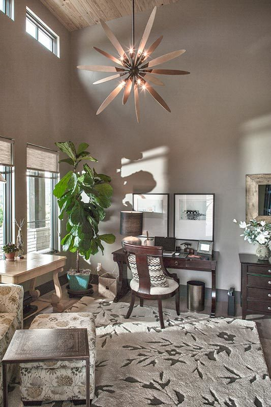 The study has a dark wood desk, floral area rug, and a statement chandelier hanging from the high vaulted ceiling.