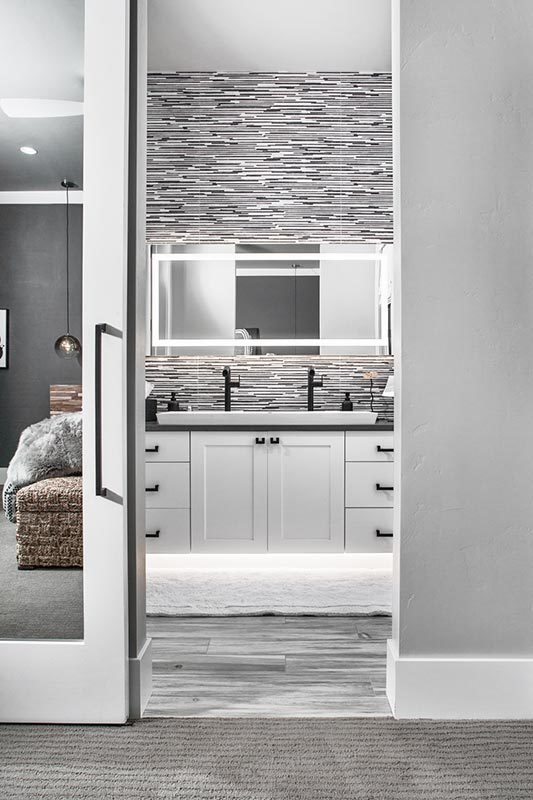 A sliding glass door opens to the bathroom with an illuminating mirror and white sink vanity contrasted with wrought iron fixtures and hardware.