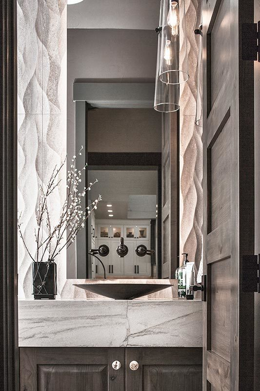 A powder room with glass sconces and a vessel sink vanity crowned with a white marble countertop.