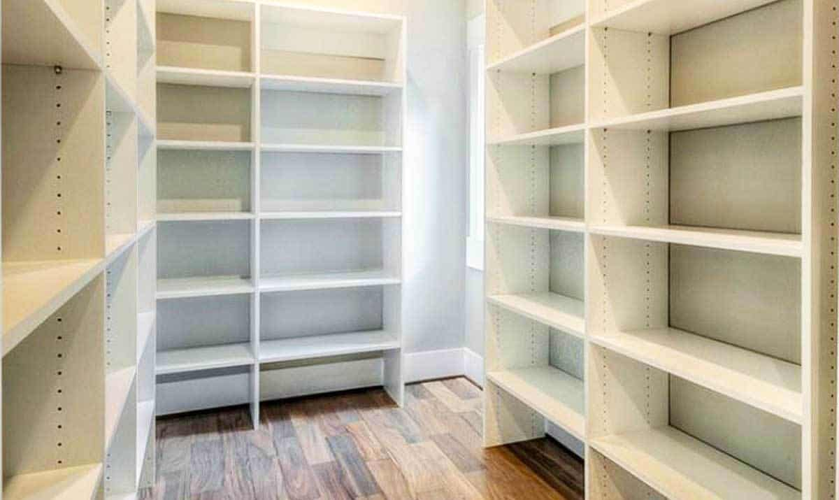 The walk-in closet is filled with built-in cabinets that blend in with the white walls.