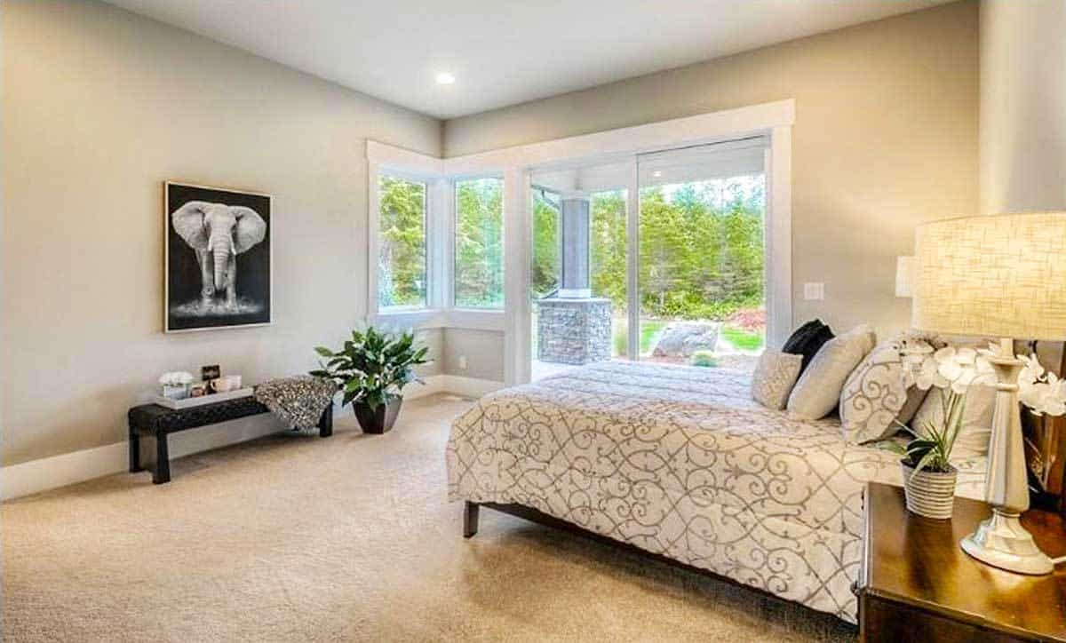 The primary bedroom has beige carpet flooring and a sliding glass door that leads out to the covered porch.