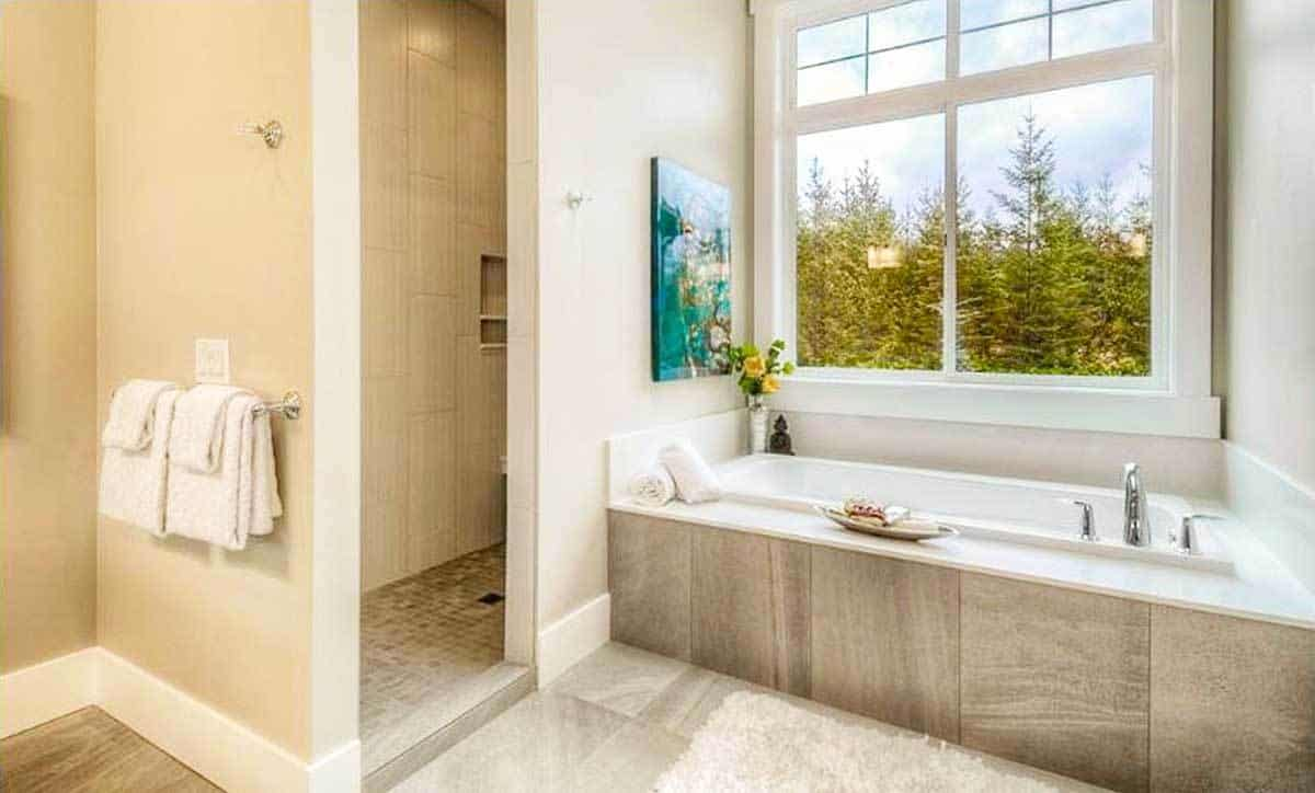 Primary bathroom equipped with a walk-in shower and a deep soaking tub adorned with a bold artwork.