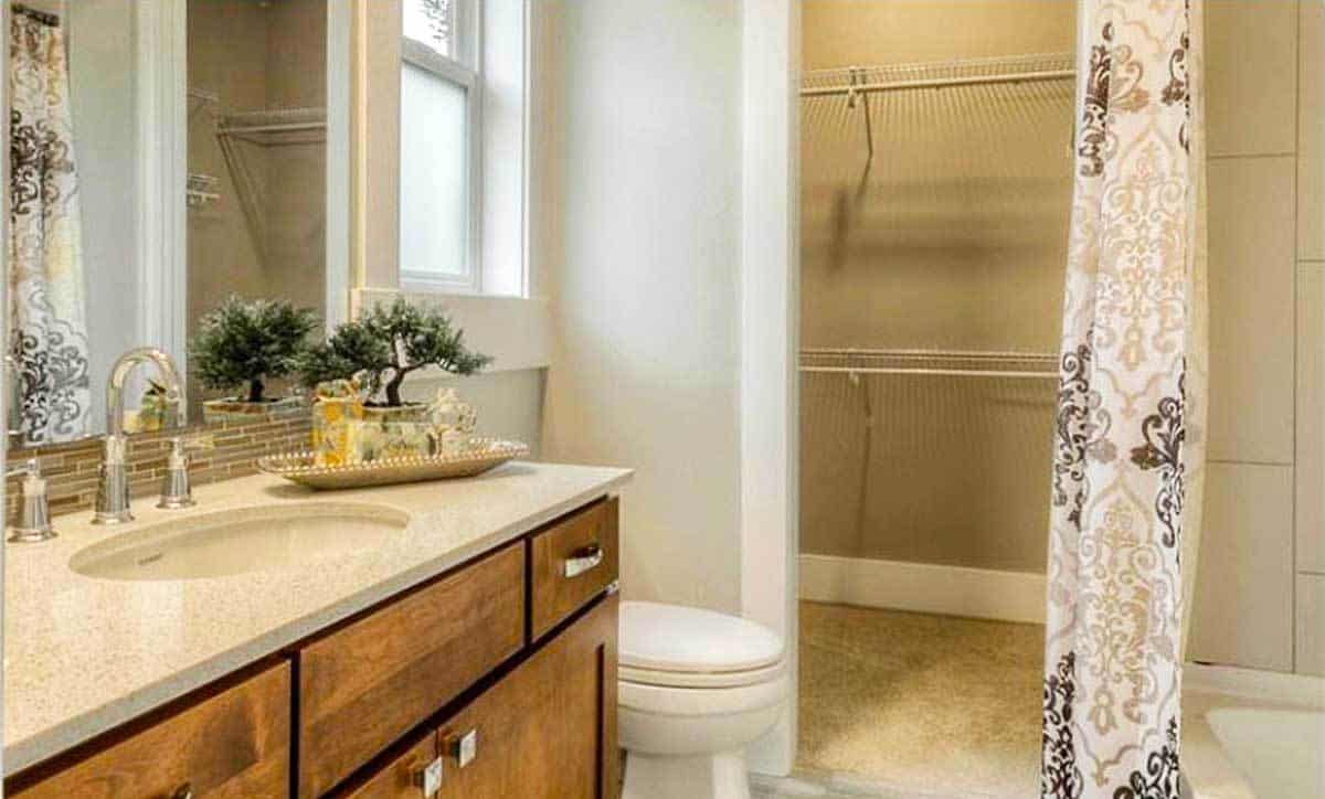 Bathroom with a toilet, sink vanity, and a tub and shower combo enclosed in a patterned curtain.