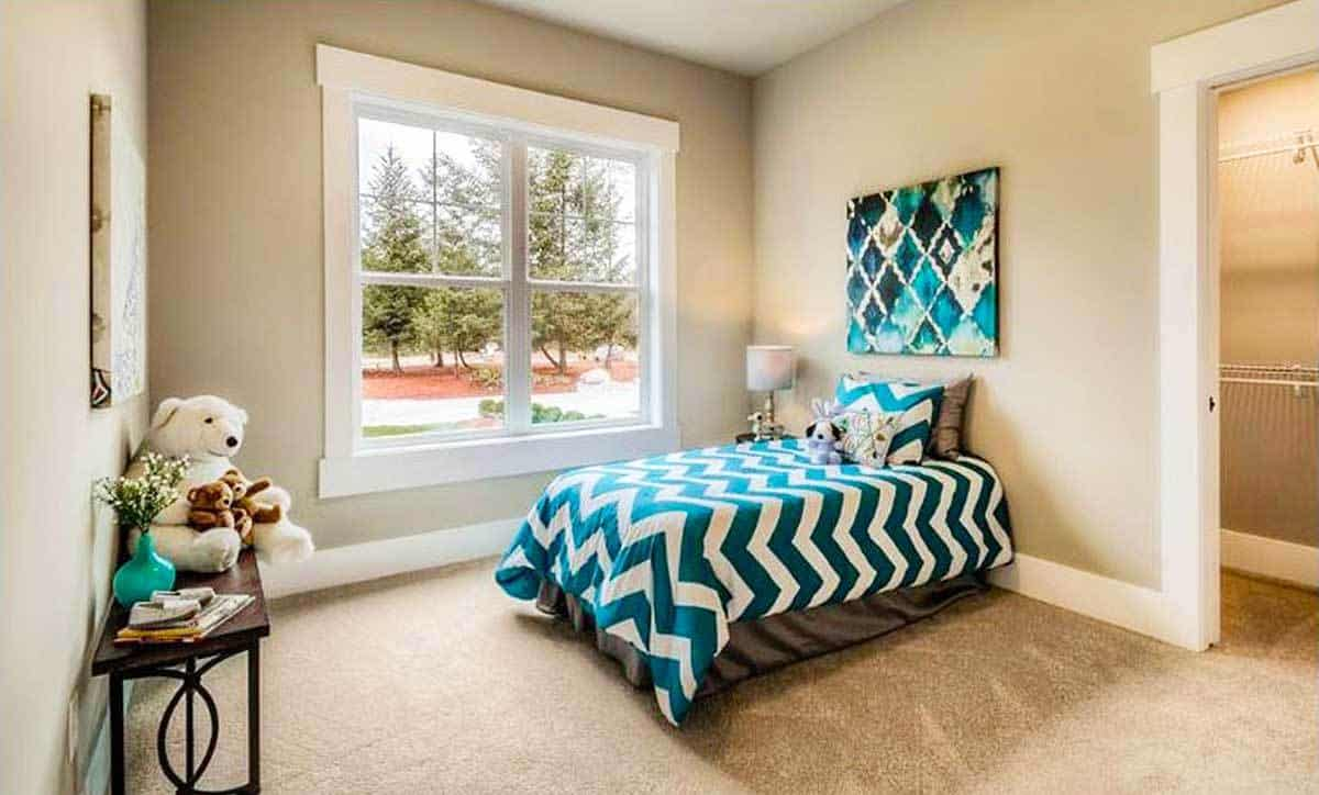 This bedroom has a wrought iron console table and a single bed accented with a green chevron comforter.