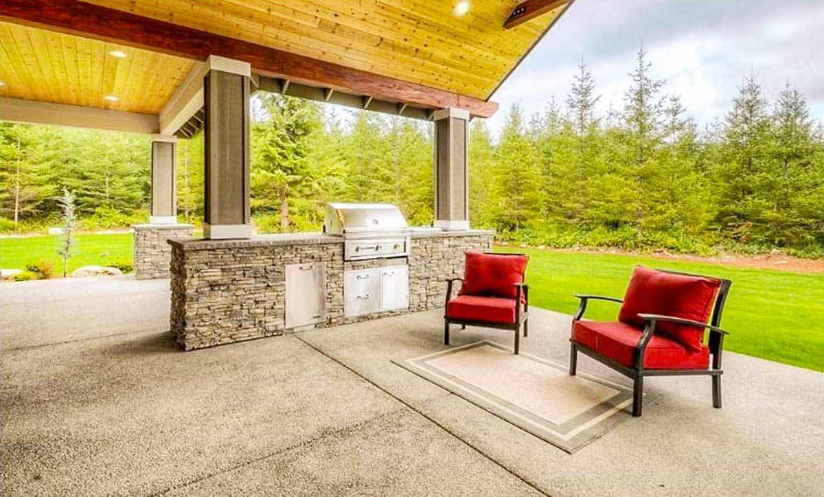 The outdoor living has red cushioned armchairs and a summer kitchen fitted on the stone half wall.