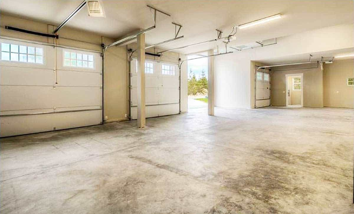 The spacious garage has concrete flooring and white doors. It can fit four cars comfortably.