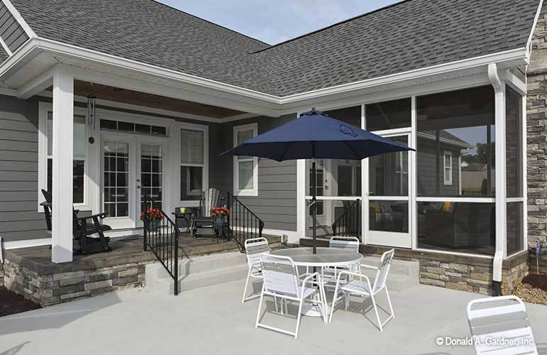 White metal armchairs under the umbrella shade sit in front of the screened porch.