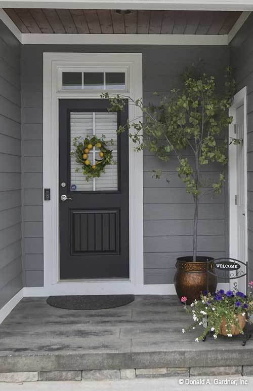 Home entry with a dark wood front door adorned with a lovely wreath.