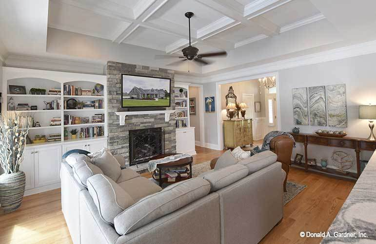 The living room has a coffered ceiling and a stone fireplace with a wall-mounted TV on top.
