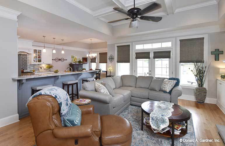 Across the V-shaped sectional is the kitchen peninsula lined with cushioned bar stools.