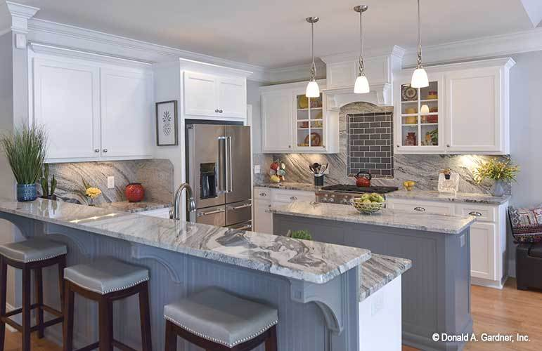 The kitchen is equipped with stainless steel appliances, a two-tier peninsula, and a slim center island lit by glass pendants.