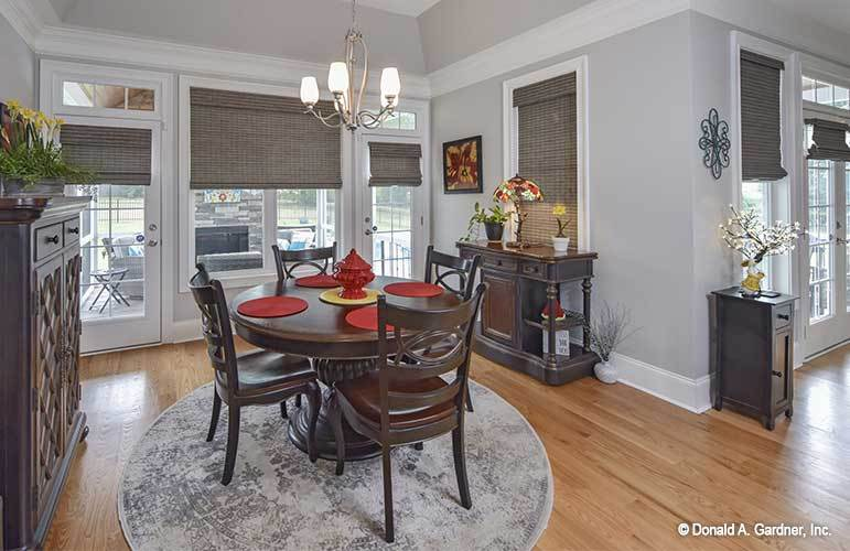 The dining area offers a dark wood buffet bar and round dining set under the chrome chandelier.