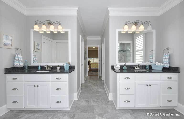 Two sink vanities with black granite countertops flank a hallway that leads to the primary bedroom.
