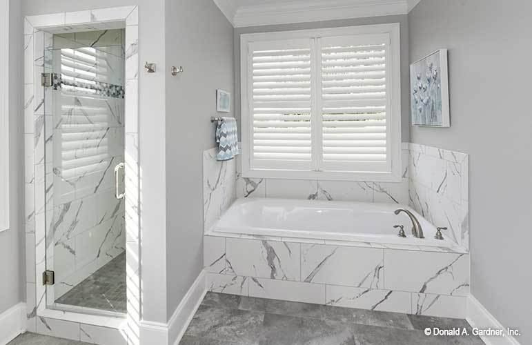 The primary bathroom is equipped with a walk-in shower and a deep soaking tub clad in white marble tiles.