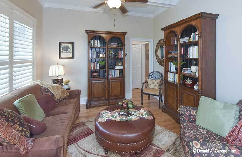 Sitting room with wooden cabinets and cozy seats paired with a round leather ottoman over a checkered rug.