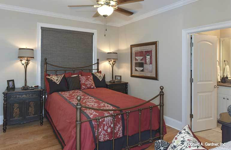 This bedroom features an ornate metal bed nestled in between the carved wood nightstands and warm table lamps.