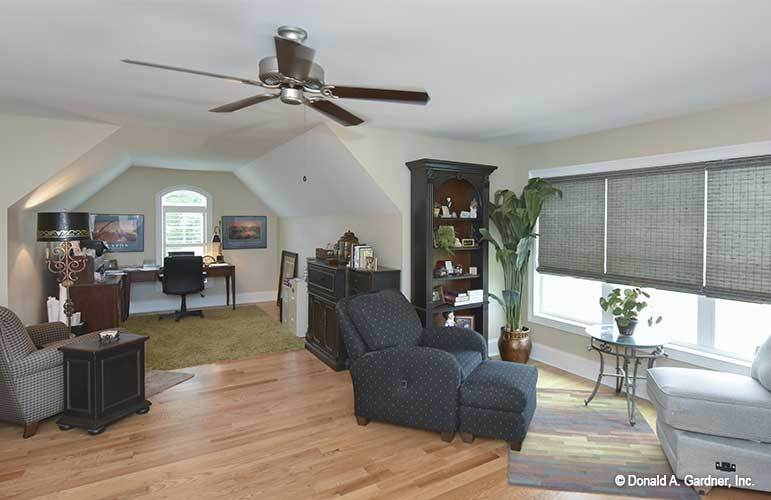 The bonus room is filled with dark wood cabinets, comfy fabric seats, and a wooden desk by the arched window complemented with a black swivel chair.