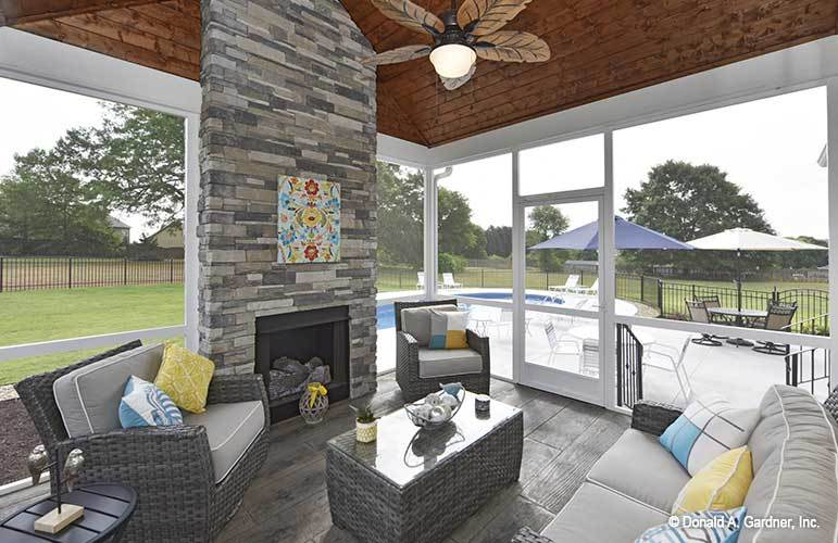 Screened porch with stylish ceiling fan, a stone fireplace, and wicker seats topped with gray cushions and multi-colored pillows.