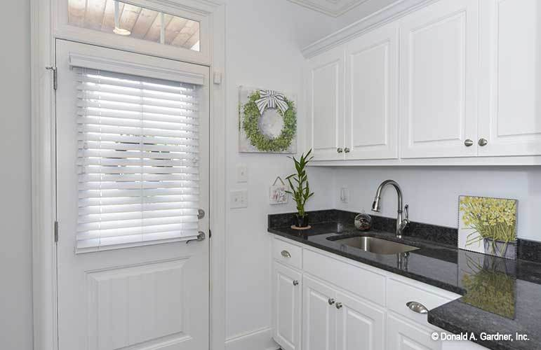 Utility room with black granite countertops and white cabinets blending in with the white walls and glazed door.