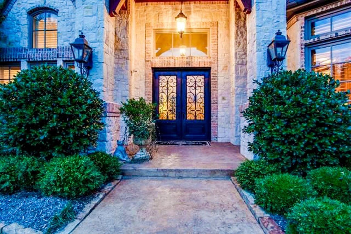 Home's entry with an ornate front french door illuminated by a warm glass pendant.