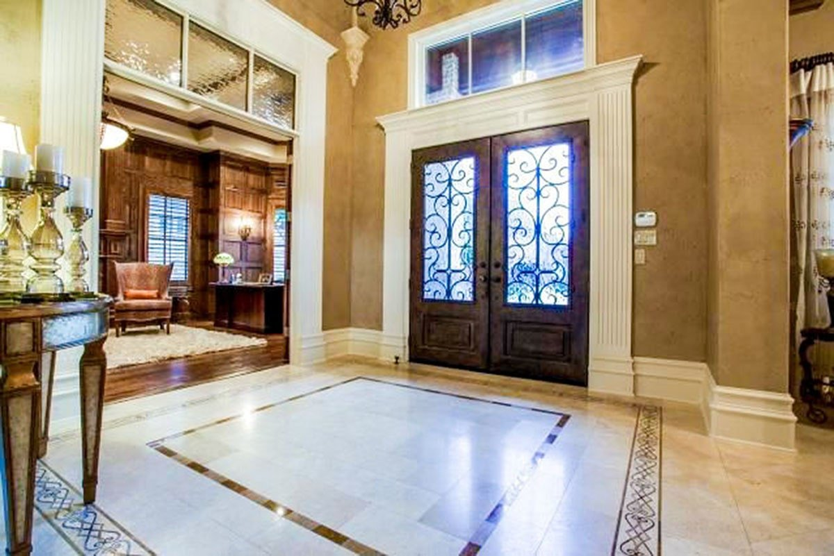 The foyer situated near the study has a limestone flooring adorned with decorative bordered decal.