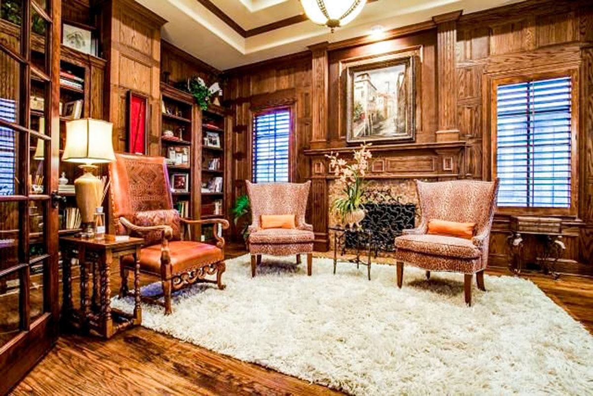 The study features a romantic fireplace and wood-paneled walls that blend in with the built-in and hardwood flooring.