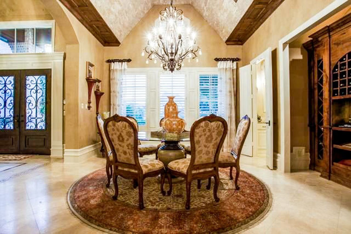 Formal dining room with floral upholstered chairs and a glass top dining table under the crystal chandelier.