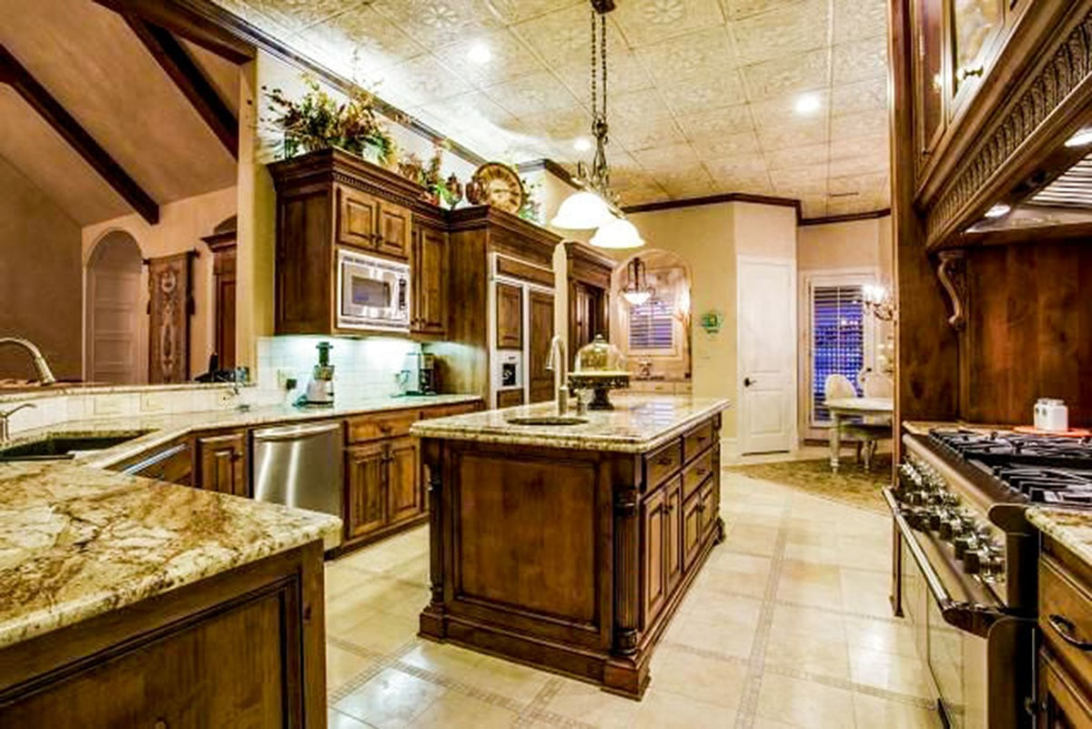 The kitchen offers natural wood cabinetry, stainless steel appliances, and a center island with granite countertop.