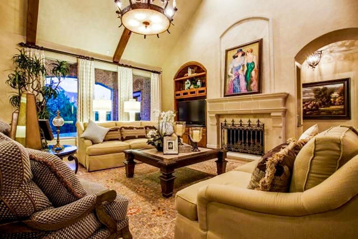 The family room has cushioned seats, a marble fireplace, and arched inset niches mounted with lovely paintings.