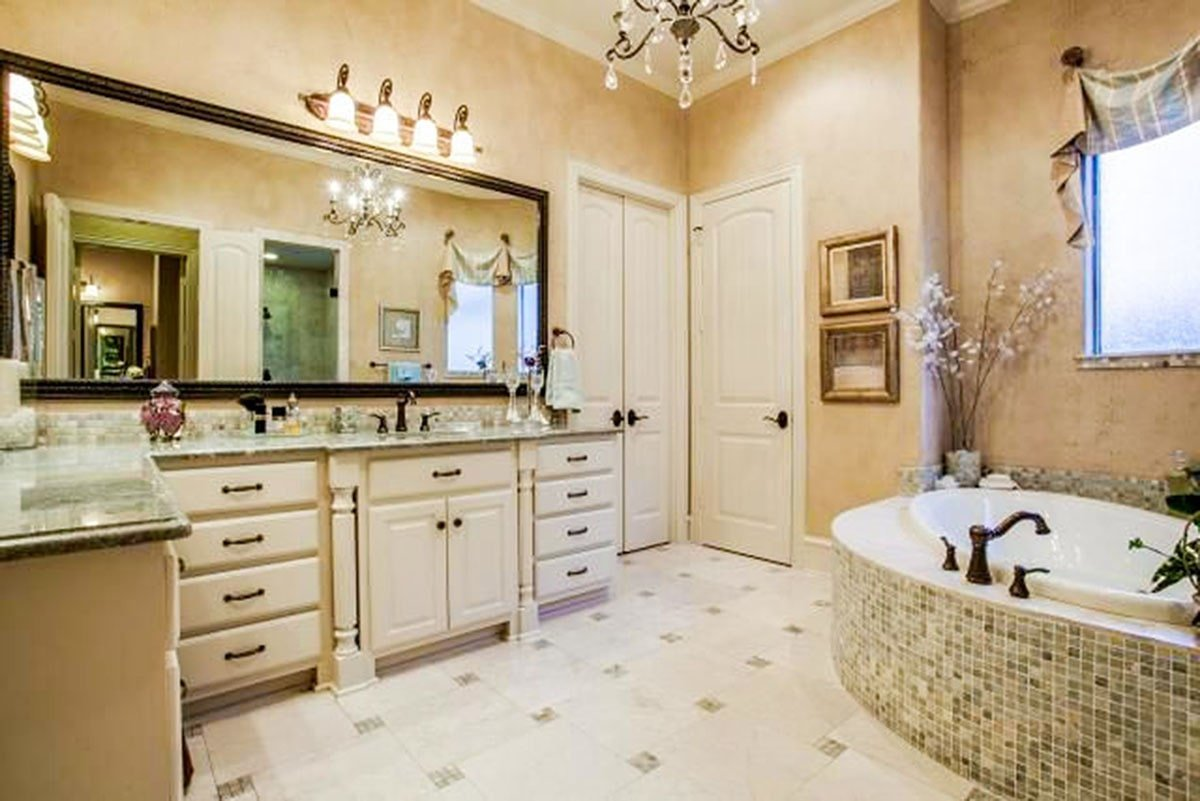 Her primary bathroom is equipped with a deep soaking tub and an L-shaped vanity topped with granite countertops.