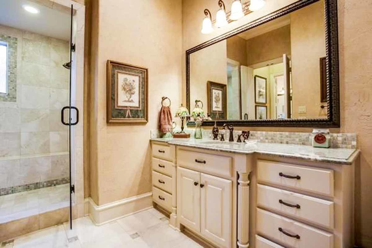 There's also a separate shower area and another sink vanity paired with a large rectangular mirror.