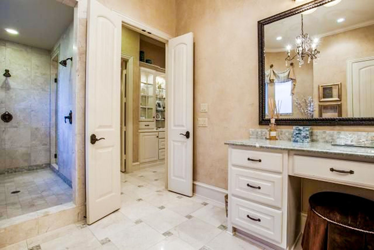 The white double door opens to his primary bathroom with a granite top vanity and a large shower area fitted with wrought iron fixtures.