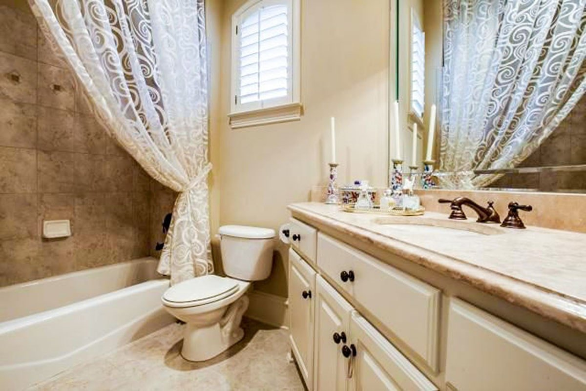 This bathroom has a shower and tub combo, a sink vanity, and a toilet fixed under the arched louvered window.