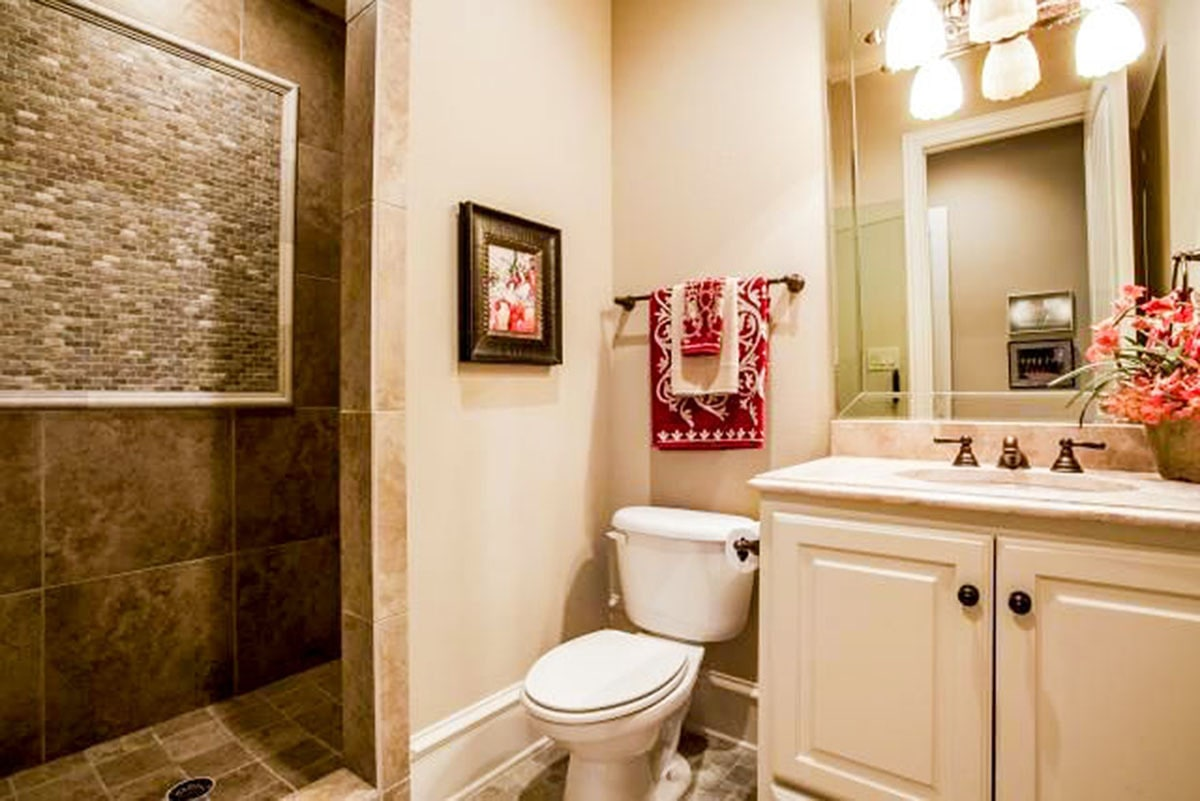 A smaller bathroom with a shower area, a toilet, and a sink vanity lit by warm glass sconces.