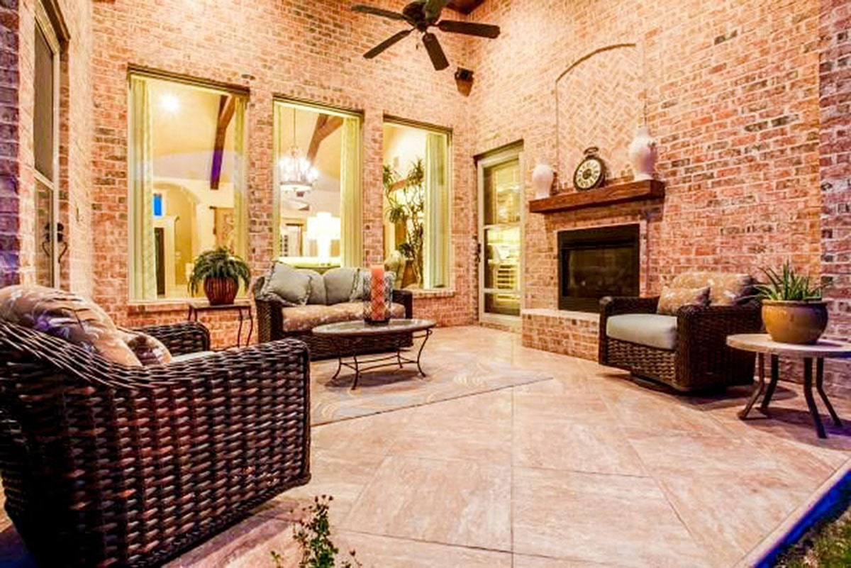 The outdoor living has a brick fireplace, round tables, and wicker seats topped with comfy cushions and fluffy pillows.