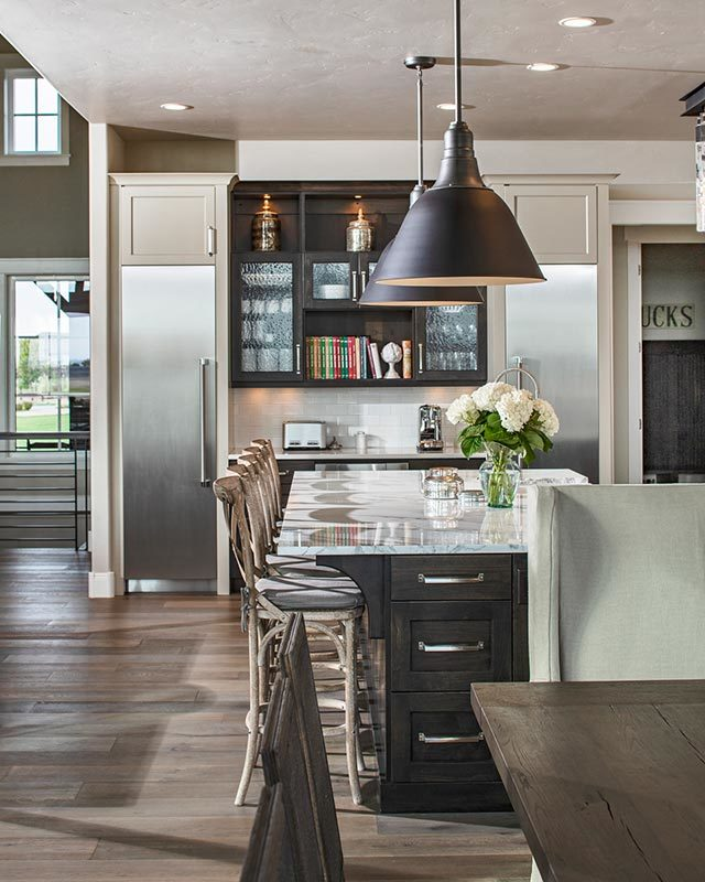 A closer look at the kitchen island with dark wood pull-outs and white marble countertop lit by oversized dome pendants.