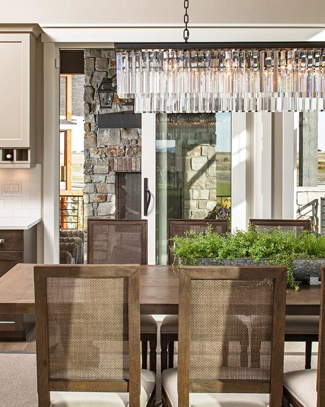The glass cascading chandelier is suspended above a rectangular dining table surrounded by wooden cushioned chairs.