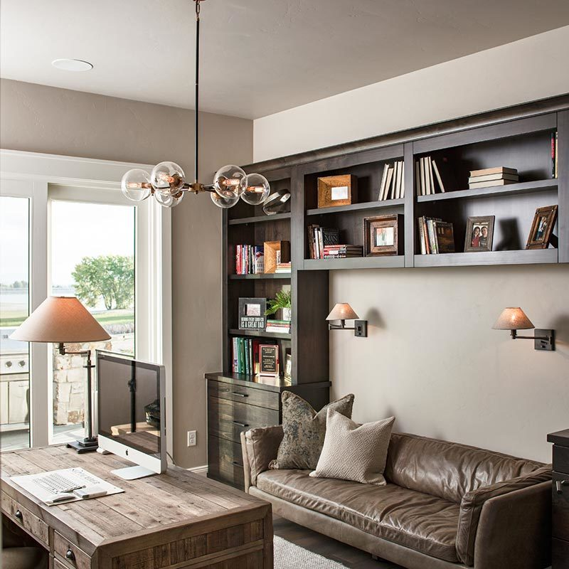 The study has a glass chandelier, a natural wood desk, and a brown leather sofa lit by warm sconces.