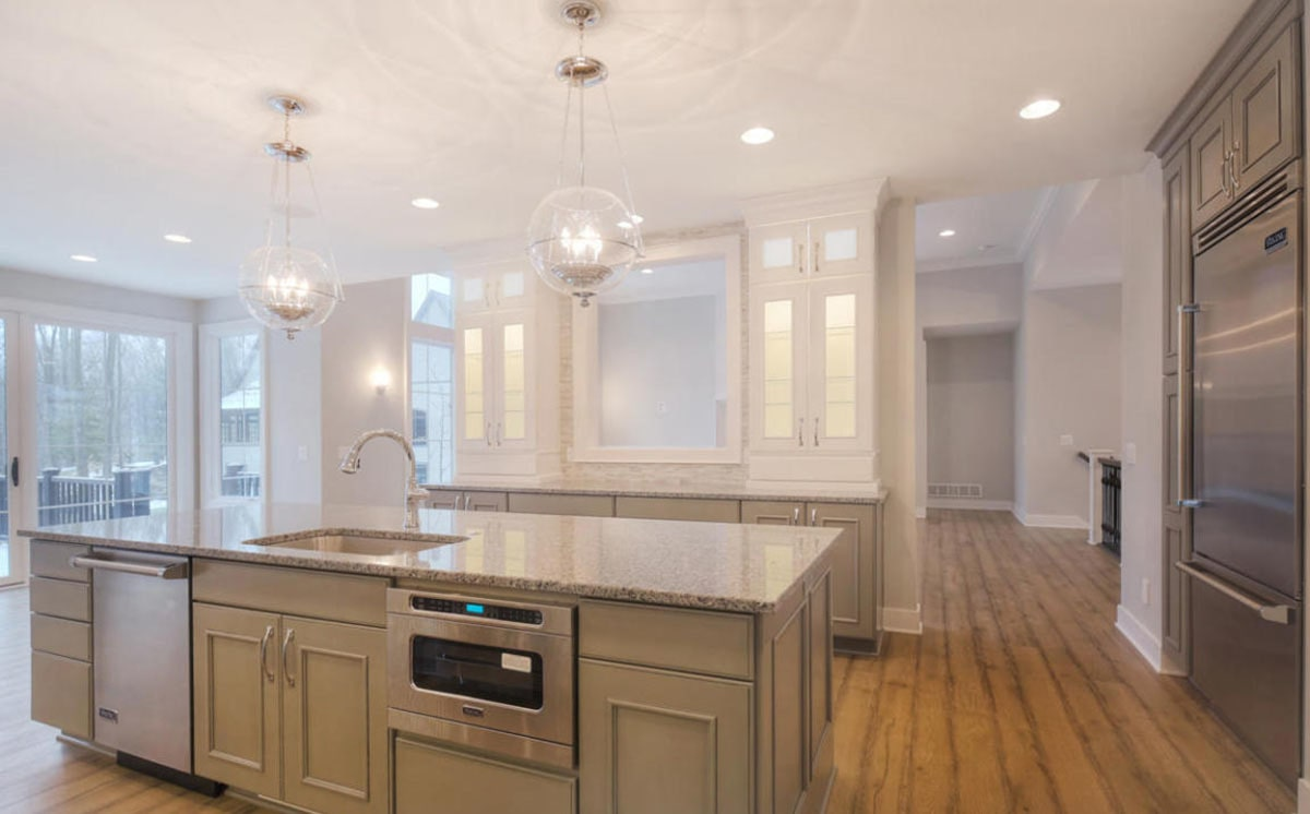 The kitchen has rustic hardwood flooring and a regular white ceiling mounted with recessed lights and a pair of glass globe pendants.