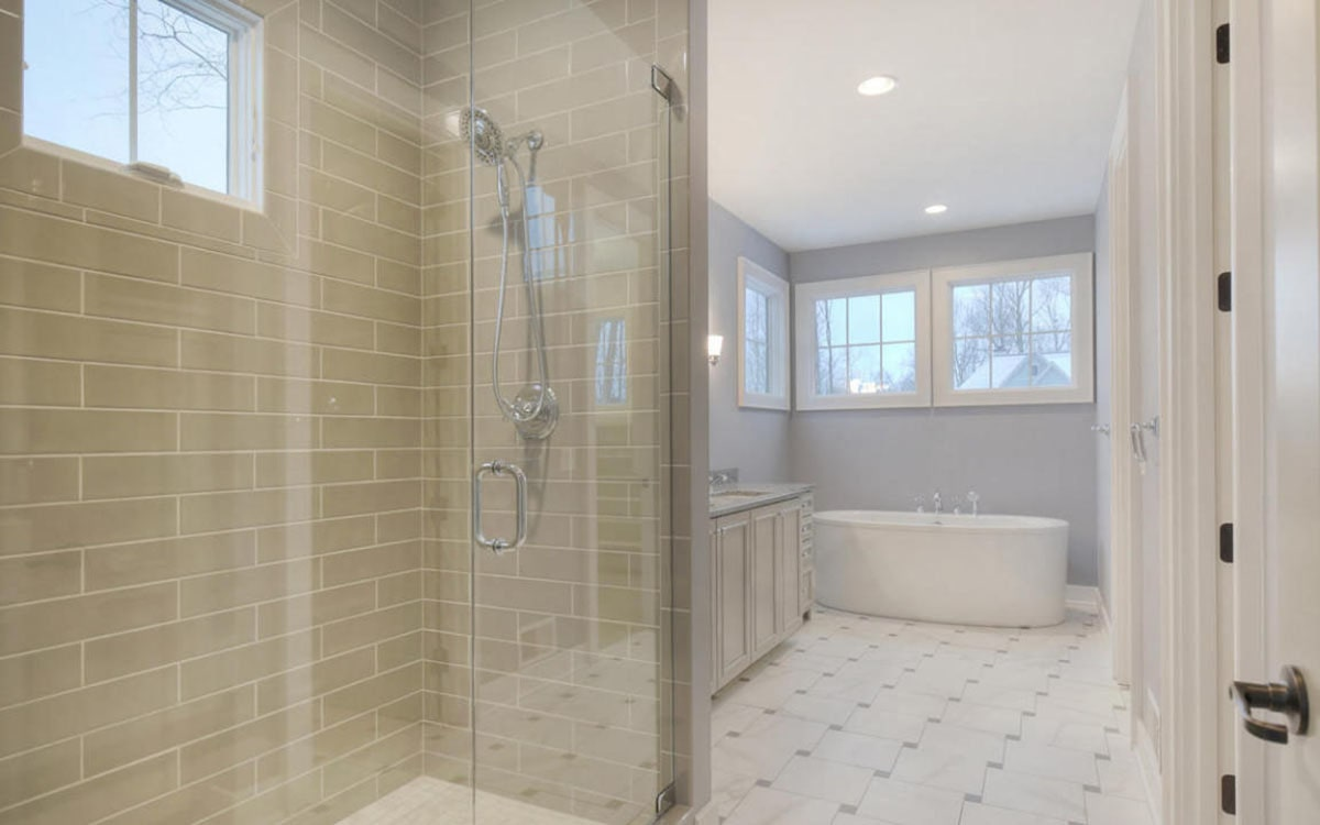 The primary bathroom is equipped with a separate shower and a freestanding tub situated against the light blue walls.