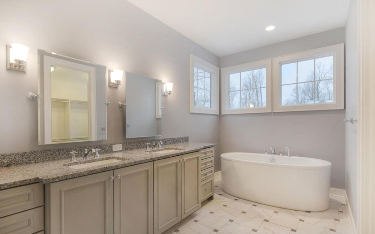 The deep soaking tub is complemented with a dual sink vanity that's topped with an elegant granite countertop.