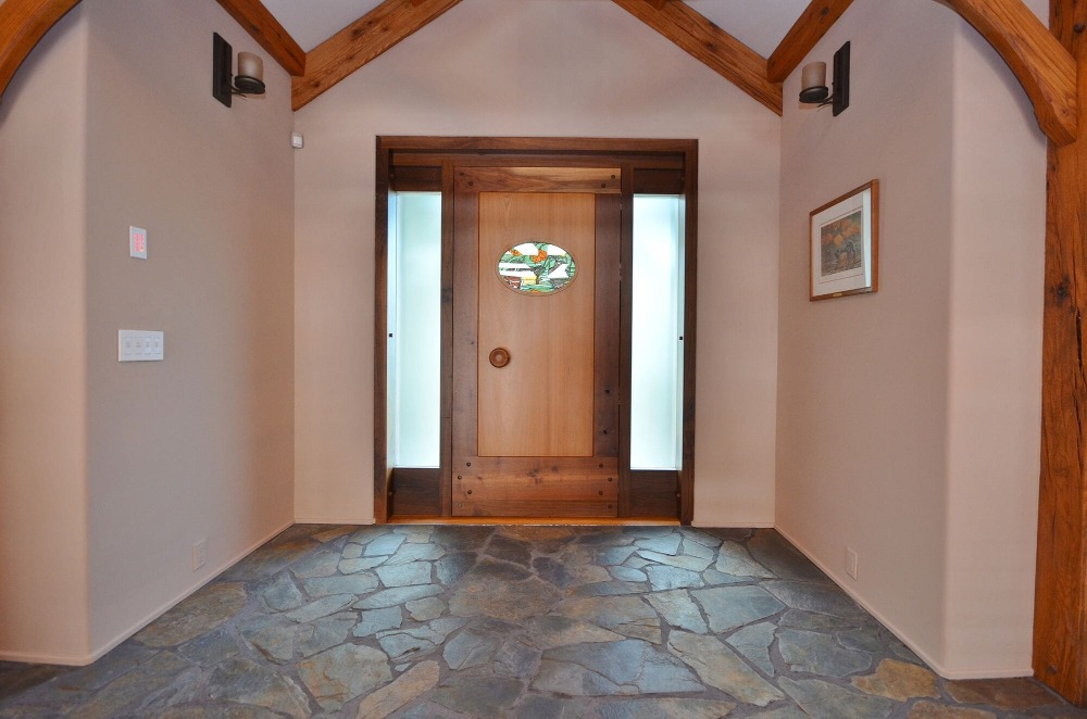 The house's entry foyer boasts stone flooring and a tall ceiling with large exposed beams. Images courtesy of Toptenrealestatedeals.com.