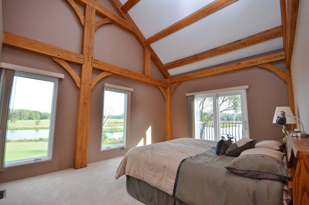 A bedroom suite with a cozy bed set along with a tall ceiling and carpeted flooring. Images courtesy of Toptenrealestatedeals.com.
